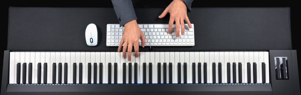 Fingers playing the keys of a piano and a computer