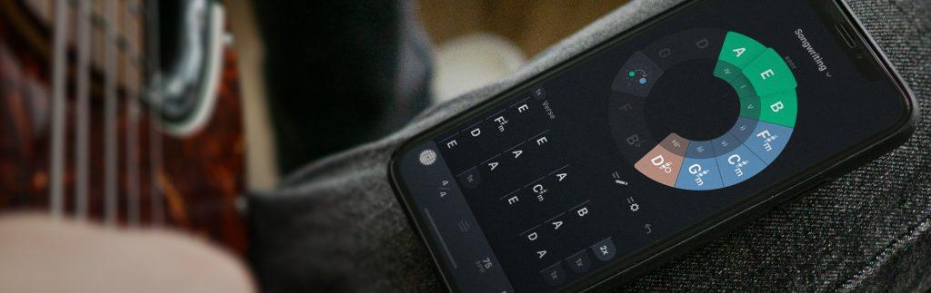 Handy mit geöffneter Songwriting App Tonaly auf dem Bein einer Musik spielenden Person